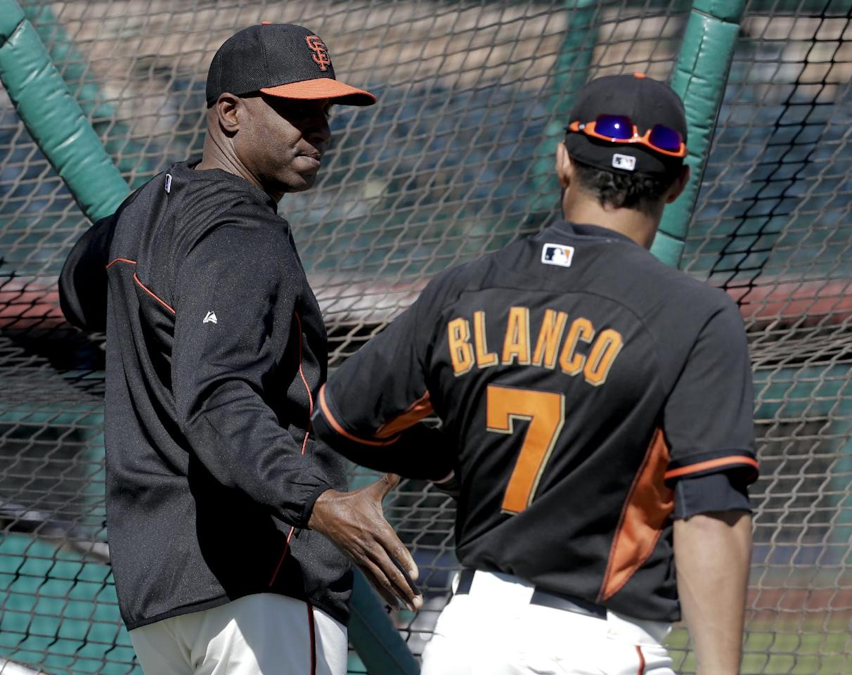 San Francisco Giants former player Barry Bonds, left, greets center fielder Gregor Blanco during batting practice before a spring training baseball game between the Giants and the Chicago Cubs in Scottsdale, Ariz., Monday, March 10, 2014. Bonds starts a seven day coaching stint today. (AP Photo/Chris Carlson)