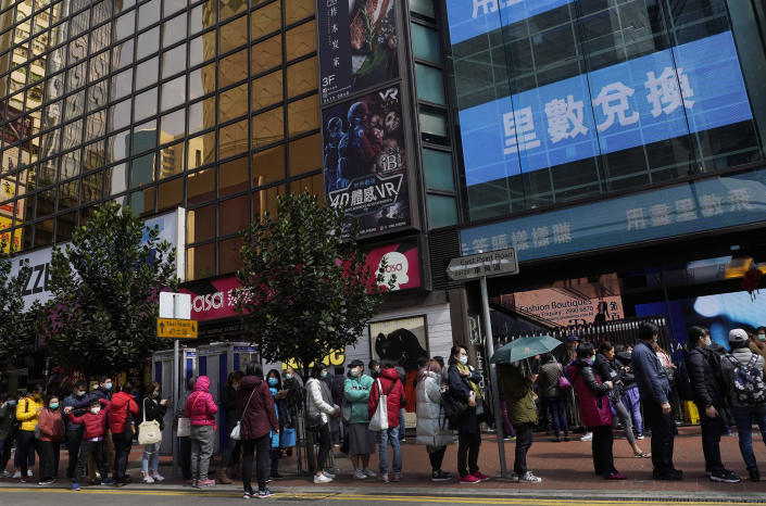 People queue up to purchase face masks outside a shop in Hong Kong, Monday, Jan. 27, 2020. Hong Kong announced it would bar entry to visitors from the mainland province at the center of the outbreak of a viral disease. Travel agencies were ordered to cancel group tours nationwide following a warning the virus's ability to spread was increasing. (AP Photo/Vincent Yu)