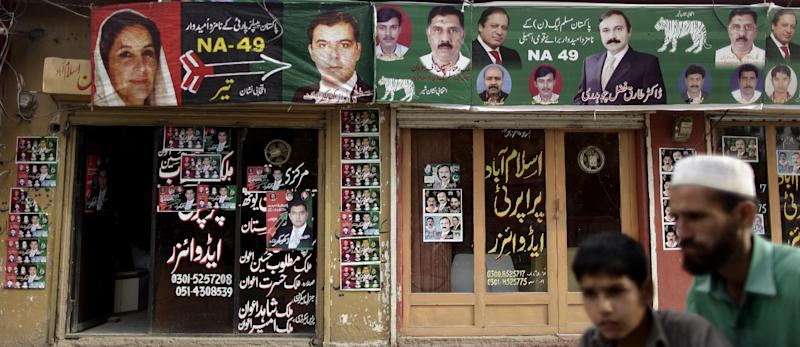 In this Tuesday, May 7, 2013, photo, offices are decorated with posters showing candidates of Pakistan People's Party (PPP), left, and candidates of Pakistan Muslim League-N party headed by Nawaz Sharif, right, in Islamabad, Pakistan. The campaign posters, fliers and commercials for the Pakistan People's Party are both advertisements for why the party has been so popular and indicate the challenges it faces in the May 11 election: two of the people on the posters are dead and another is not old enough to run in the election. (AP Photo/Muhammed Muheisen)