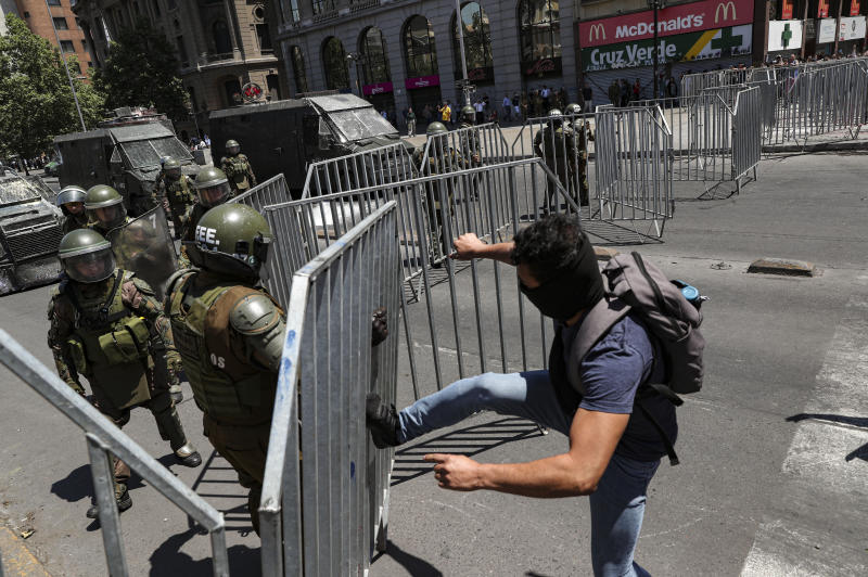 An anti-government demonstrator kicks a police barricade near to La Moneda presidential palace in Santiago, Chile, Tuesday, Nov. 12, 2019. Students in Chile began protesting nearly a month ago over a subway fare hike. The demonstrations have morphed into a massive protest movement demanding improvements in basic services and benefits, including pensions, health, and education. (AP Photo/Esteban Felix)