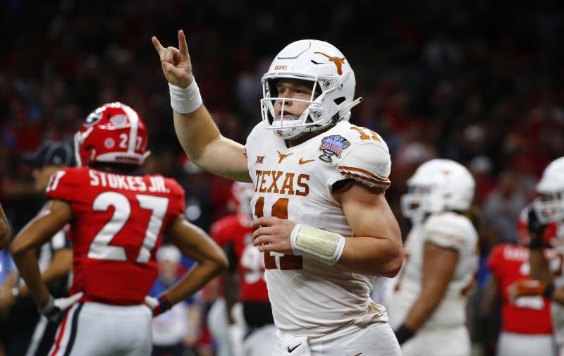 FILE - In this Tuesday, Jan. 1, 2019 file photo, Texas quarterback Sam Ehlinger (11) celebrates his second touchdown carry in the first half of the Sugar Bowl NCAA college football game against Georgia in New Orleans. The hits came at Sam Ehlinger from just about every angle this summer. Baker Mayfield jabbed him first. Then Terry Bradshaw landed one. Texas junior quarterback didnt seem to mind, and will likely care even less every time he gets to flash a Hookem horns hand sign after scoring a touchdown. Which he does a lot. Ehlinger and the Longhorns are expected to again challenge for the Big 12 title in 2019. (AP Photo/Butch Dill, File)