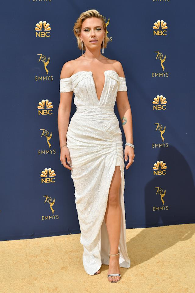 <p>Scarlett Johansson walked the gold carpet in a white sequined gown with a high slit and plunging neckline. The off-the-shoulder design showed off her floral back tattoo. She accessorized simply with dangling earrings and a matching bracelet, and styled her blonde lob slicked back. (Photo: Shutterstock) </p>