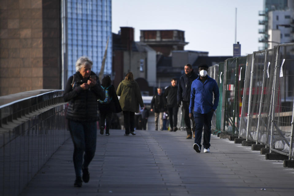 Commuters, some wearing protective masks to protect against coronavirus walk on London Bridge, in London, Monday, May 18, 2020. Britain's Prime Minister Boris Johnson announced last Sunday that people could return to work if they could not work from home. (AP Photo/Alberto Pezzali)