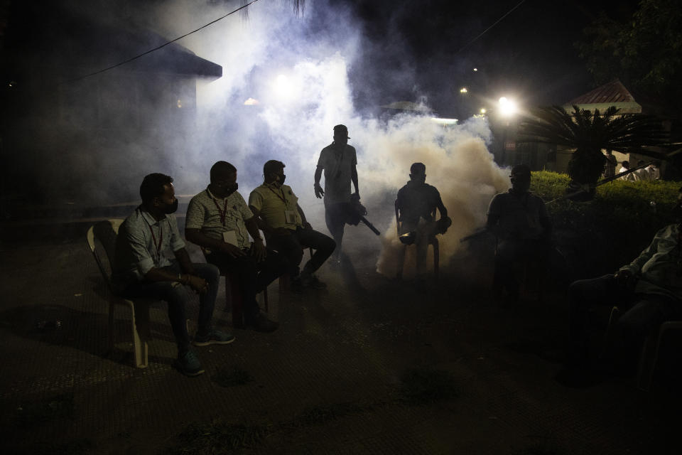 A municipal worker fumigates as supporters of Bharatiya Janata Party wait outside a vote counting center in Gauhati, India, Sunday, May 2, 2021. Preliminary voting trends released by India's electoral body on Sunday indicate Prime Minister Narendra Modi's Hindu nationalist party failed to make gains in four recent state elections, a sign his political strength may be slipping as the country struggles to contain an unprecedented surge in coronavirus cases. (AP Photo/Anupam Nath)