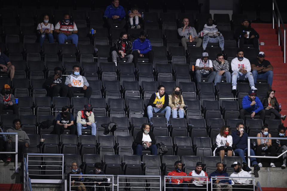 Basketball fans watch during the first half of an NBA basketball game between the Washington Wizards and the Golden State Warriors, Wednesday, April 21, 2021, in Washington. (AP Photo/Nick Wass)