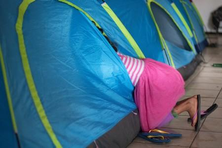 Flor, a 9-year old Guatemalan girl returned to Mexico to await her asylum hearing, dives into a tent in a migrant shelter in Tijuana