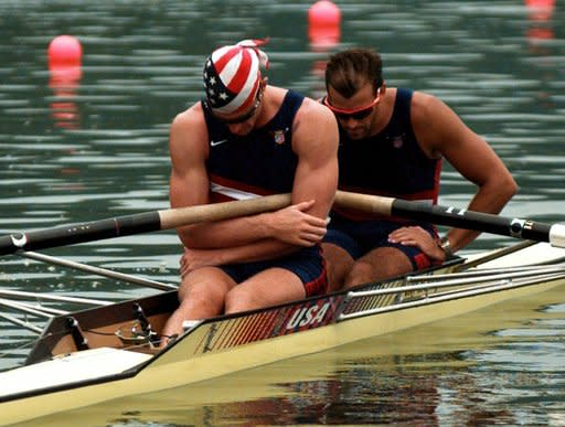 FILE - In this Saturday, July 27, 1996, file photo, American's Jonathan Holland, left, and Michael Peterson pause for a moment of silence for those killed and injured in an explosion at Atlanta's Olympic Centennial Park Saturday morning, before their men's coxless pair race at Lake Lanier near Gainesville, Ga. (AP Photo/Tannen Maury)