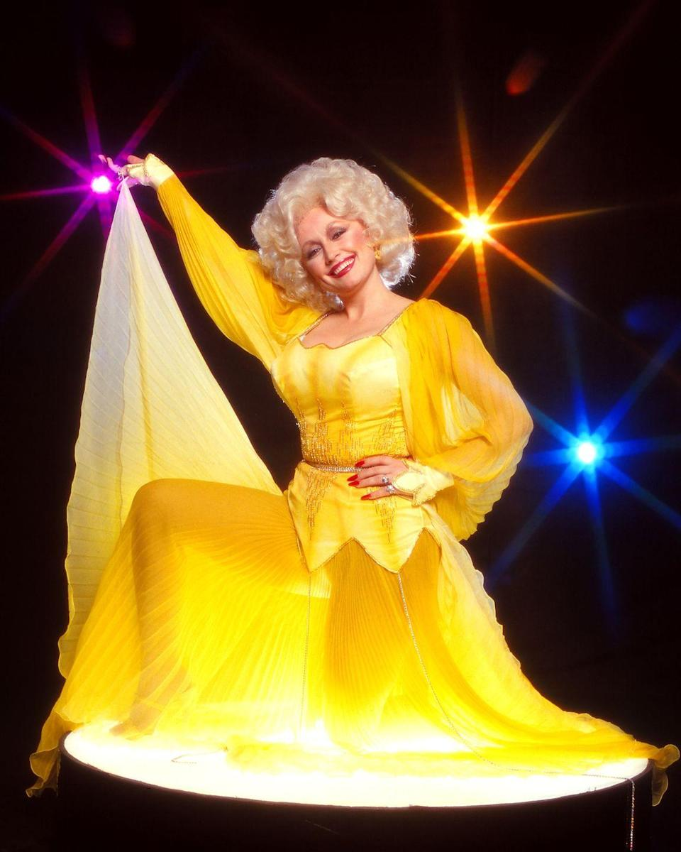"""<p>If sunshine were a person, it would be Parton in this striking yellow gown. In 2016, Parton would <a href=""""https://www.huffpost.com/entry/dolly-parton-cmas_n_581b2c45e4b01a82df64e758"""" data-ylk=""""slk:wear a similar look"""" class=""""link rapid-noclick-resp"""">wear a similar look </a>while picking up the Willie Nelson Lifetime Achievement award at the Country Music Awards. </p>"""