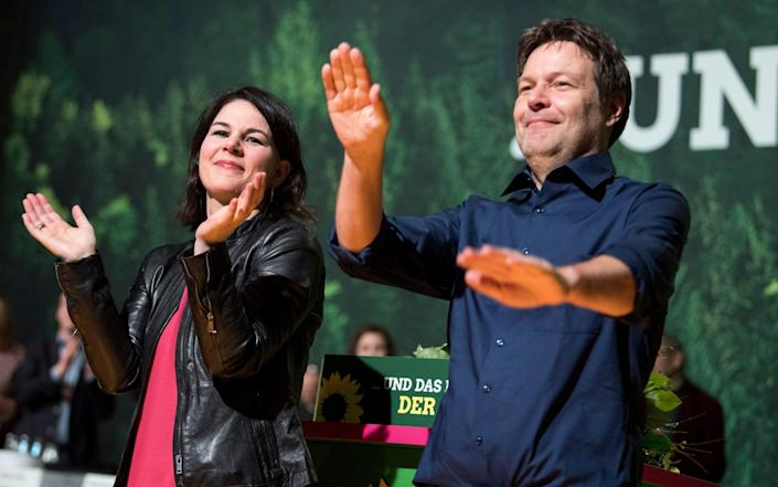 Annalena Baerbock in a pink t-shirt and leather jacket and her Green party co-leaderRobert Habeck clap and celebrate during a national party convention - Bernd von Jutrczenka/dpa via AP