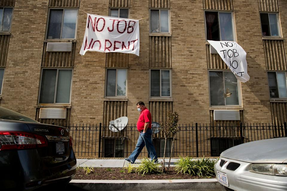"""Signs that read """"No job, no rent"""" hang from the windows of an apartment building in northwest Washington, D.C., in May. The pandemic shut housing courts and prompted policies protecting renters from eviction. But not everyone is covered, and now many are coming to an end. (Photo: Andrew Harnik/Associated Press)"""