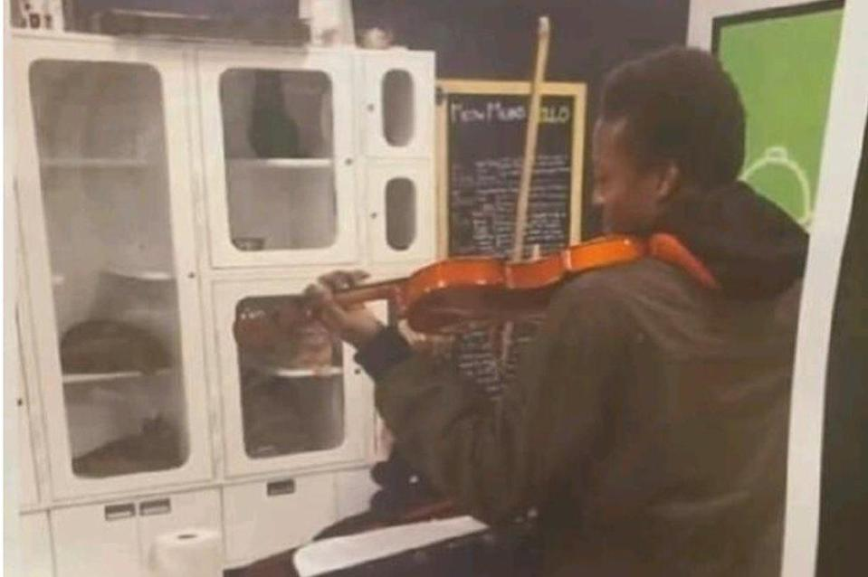 Mr McClain playing violin to cats in a shelter