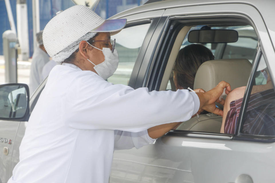 MACEIÓ, AL - 30.03.2020: DRIVE THRU VACINOU MAIS DE DEZ MIL IDOSOS - In just five days, the drive thru vaccination system of two major malls in Maceió, until yesterday, vaccinated 10,522 of the target audience of the first phase of the campaign against influenza. Throughout the capital, 60% of the elderly have already been vaccinated, according to the Municipal Health Department of Maceió. In the photo, health professionals carry out the vaccine for the elderly, inside their own cars, on the drive thru system in a mall in the capital. (Photo: GUIDO JR./Fotoarena/Sipa USA)(Sipa via AP Images)