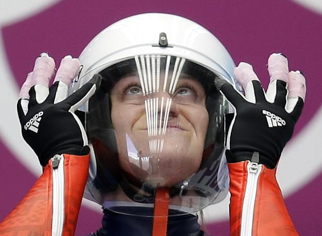 Natalja Khoreva of Russia adjusts her helmet as she prepares for a run during a training session for the women's singles luge at the 2014 Winter Olympics, Saturday, Feb. 8, 2014, in Krasnaya Polyana, Russia. (AP Photo/Natacha Pisarenko)