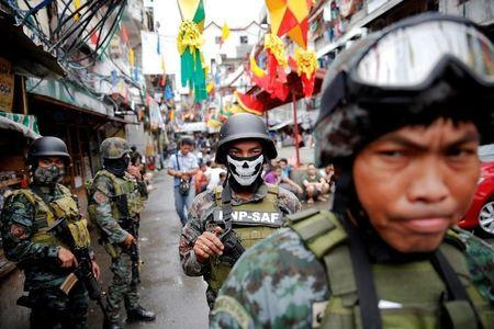 Armed security forces take a part in a drug raid, in Manila