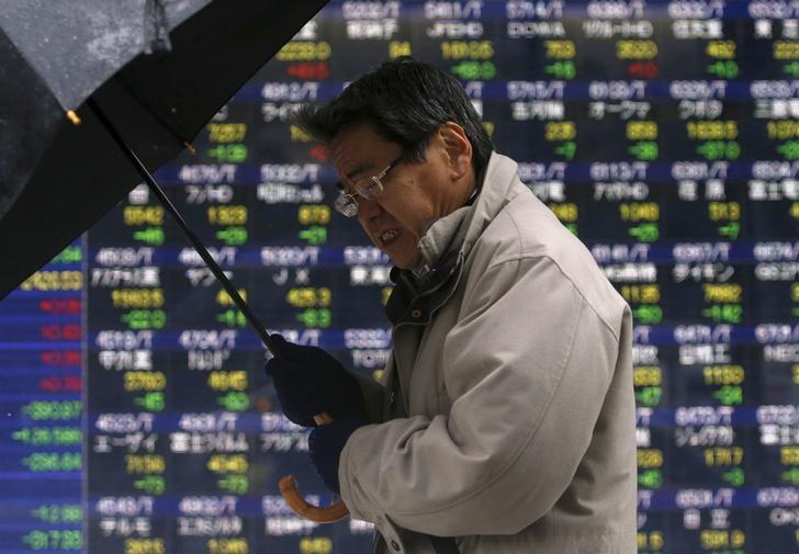 A pedestrian holding an umbrella walks past an electronic board showing the various stock prices outside a brokerage in Tokyo, Japan, January 18, 2016. REUTERS/Yuya Shino/Files