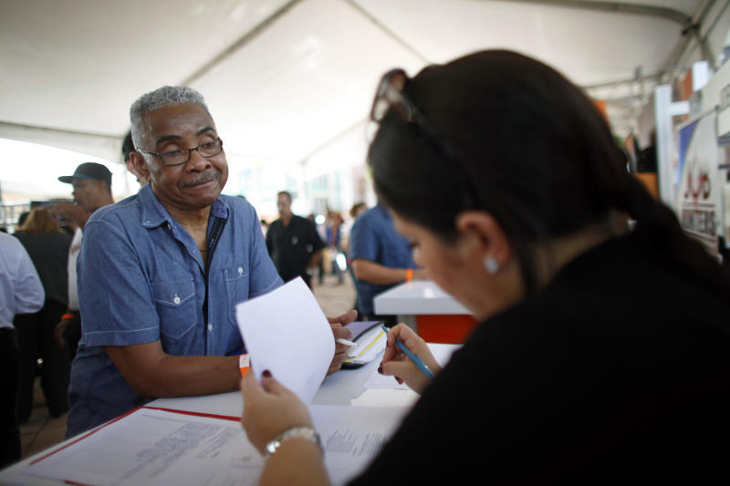 """In this Sept. 25, 2013 photo, Gilberto Olivo talks with a representative at a job fair in Catano, Puerto Rico. Olivo is a chemical engineer who held managerial positions in the U.S. and Puerto Rico before losing his job five years ago. """"I'll do anything,"""" he said. """"I'll clean floors, I'll wash dishes, I'll be an errand boy."""" (AP Photo/Ricardo Arduengo)"""