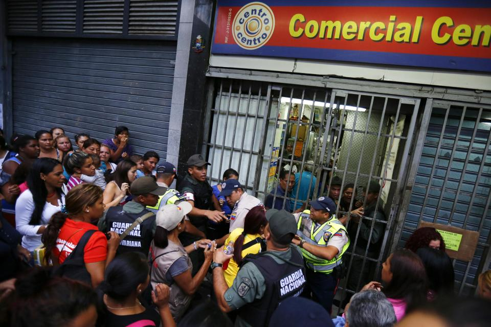 People line up to buy toilet paper and baby diapers as national guards control the access at a supermarket in downtown Caracas January 19, 2015. There's a booming new profession in Venezuela: standing in line. The job usually involves starting before dawn, enduring long hours under the Caribbean sun, dodging or bribing police, and then selling a coveted spot at the front of huge shopping lines. As Venezuela's ailing economy spawns unprecedented shortages of basic goods, panic-buying and a rush to snap up subsidized food, demand is high and the pay is reasonable. Picture taken January 19, 2015. REUTERS/Jorge Silva (VENEZUELA - Tags: POLITICS BUSINESS SOCIETY)