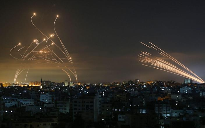 Rockets are seen in the night sky fired towards Israel from Beit Lahia in the northern Gaza Strip - ANAS BABA/AFP