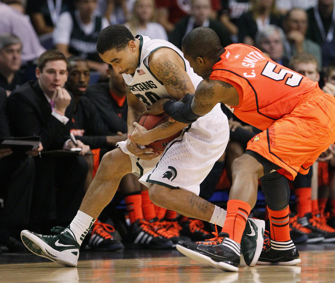 Michigan State's Brandon Wood, left, and Louisville's Chris Smith (5) vie for the ball during the first half of an NCAA men's college basketball tournament West Regional semifinal, Thursday, March 22, 2012, in Phoenix. (AP Photo/Matt York)