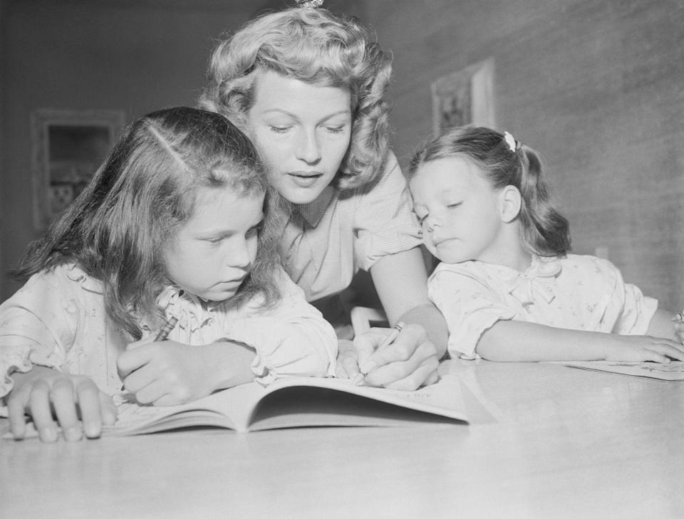 <p>Rita colors with her daughters, Rebecca and Yasmin, in 1953 at the Sands Hotel in Las Vegas.</p>