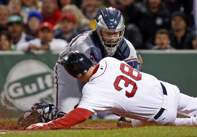 Atlanta Braves catcher Evan Gattis puts the tag on Boston Red Sox's Grady Sizemore (38) who is out trying to score on a fielder's choice in the sixth inning of a baseball game at Fenway Park in Boston, Wednesday, May 28, 2014. (AP Photo/Elise Amendola)