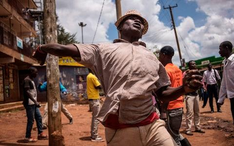 A protester hurls a stone at the police during a standoff between Kenyan police and supporters of Kenyan opposition leader - Credit: FREDRIK LERNERYD/ AFP