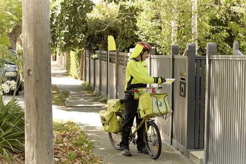 An Australia Post worker is pictured on a bike.