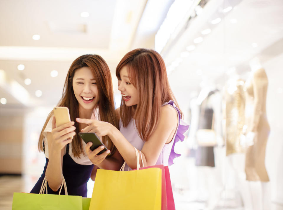 Two young women check a smartphone while shopping.