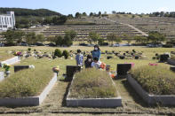 Family members wearing face masks pay respects to their ancestral cemetery ahead of Chuseok holiday, the Korean version of Thanksgiving Day, at a cemetery in Paju, South Korea, Sunday, Sept. 27, 2020. South Korea's national cemeteries will be closed during the upcoming Chuseok holiday during the five-day holidays from Sept. 30 to Oct. 4 to prevent the spread of the coronavirus.(AP Photo/Ahn Young-joon)