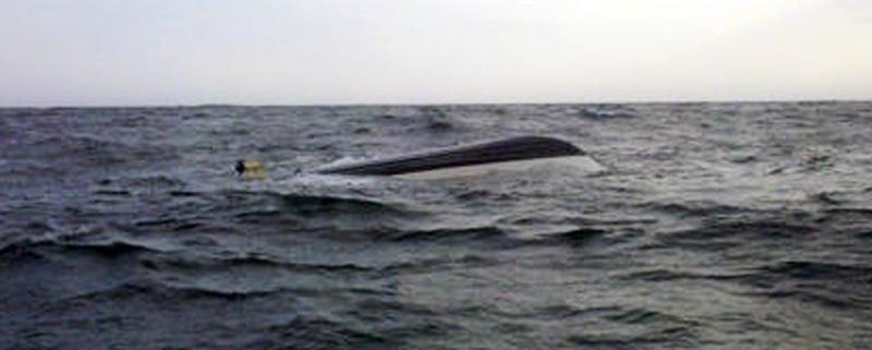 In this Friday, Sept. 30 photo provided by the US Coast Guard, the capsized boat of paraplegic skipper Nicholas Masi III, of Biddeford, Maine, is seen off the Maine coast after it rolled,about 5 miles from Kennebunkport.  It is reported that the 24-foot  boat rolled over Friday and one of the tuna fishermen died in the incident. Masi III is being credited with actions that helped save the lives of all but one crew member on his fishing boat as it took on water in rough seas off Maine. (AP Photo/U.S. Coast Guard, Mark Coady)