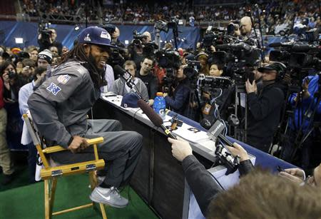 Seattle Seahawks cornerback Richard Sherman is surrounded by cameras during Media Day for Super Bowl XLVIII at the Prudential Center in Newark