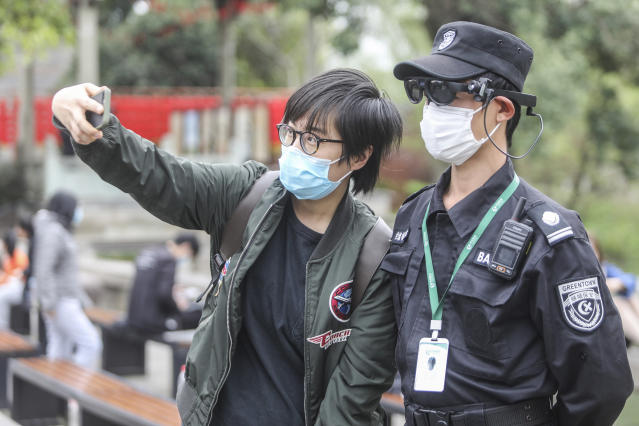 A masked tourist takes a selfie with a security guard in Xixi Wetland Park in Hangzhou, China, on 24 March. (Getty Images)