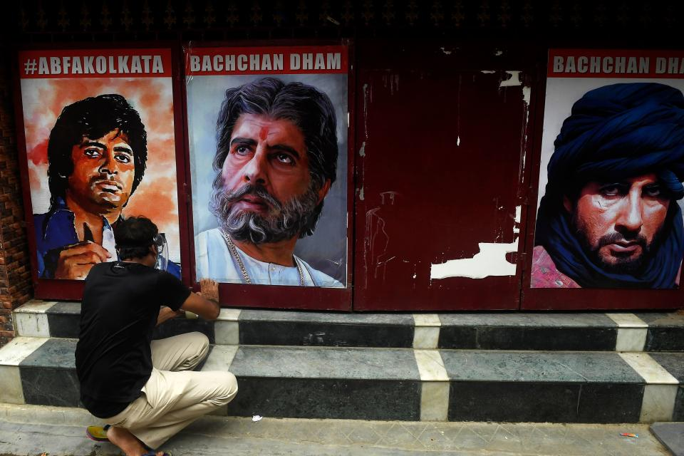 A fan of Bollywood actor Amitabh Bachchan hangs posters of the actor at the gate of All Bengal Amitabh Bachchan Fan Club in Kolkata on July 12, 2020. - Bollywood megastar Amitabh Bachchan, 77, tested positive for COVID-19 on July 11 and was admitted to hospital in Mumbai, with his actor son Abhishek -- who also announced he had the virus -- saying both cases were mild. (Photo by Dibyangshu SARKAR / AFP)