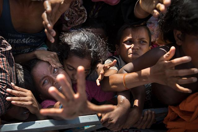 <p>Desperate Rohingya grab for aid handouts of clothing and food on September 15, 2017, in Tankhali, Bangladesh. (Photograph by Paula Bronstein/Getty Images) </p>