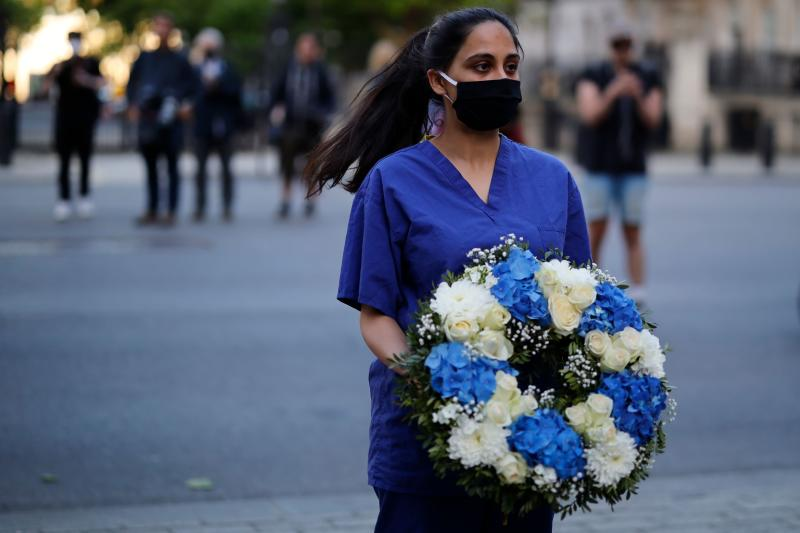 "A doctor joins a silent protest during a national ""clap for carers"" to show thanks for the work of Britain's NHS (National Health Service) workers and other frontline medical staff around the country as they battle with the novel coronavirus pandemic, outside Downing Street in London on May 28, 2020. (Photo by Tolga Akmen / AFP) (Photo by TOLGA AKMEN/AFP via Getty Images)"