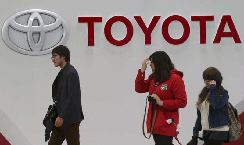Visitors walk at Toyota gallery in Tokyo Tuesday, Feb. 4, 2014. Toyota Motor Corp. reported a more than fivefold jump in its quarterly profit Tuesday and raised its earnings forecast, crediting a weak yen and strong sales. Toyota's profit for the October-December quarter totaled a better-than-expected 525.4 billion yen ($5.2 billion), up dramatically from 99.9 billion yen a year earlier. (AP Photo/Koji Sasahara)