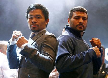 """Philippine boxing icon Manny """"Pacman"""" Pacquiao and welterweight world title holder Lucas Matthysse pose for photographers during a news conference for their upcoming WBA """"regular"""" welterweight title fight, at a hotel in Kuala Lumpur, Malaysia April 20, 2018. REUTERS/Lai Seng Sin"""