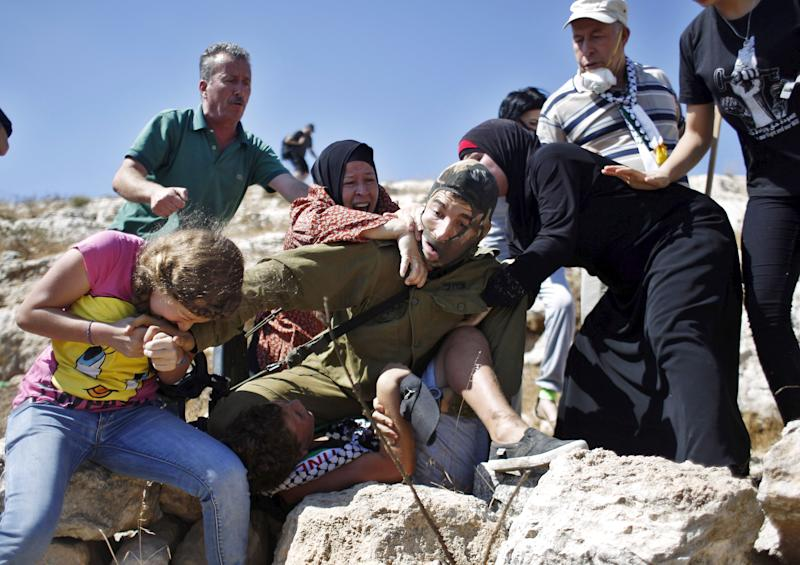 Palestinians scuffle with an Israeli soldier