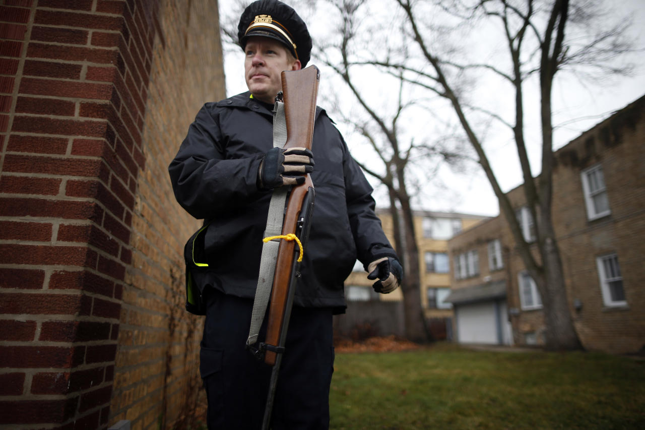 An Evanston police officer holds a firearm that was turned in as part of an amnesty-based gun buyback program in Evanston, Illinois December 15, 2012. Residents were given $100 for each operational firearm given in and no criminal charges were laid.    REUTERS/Jim Young (UNITED STATES - Tags: CRIME LAW)