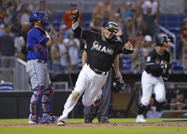 Miami Marlins shortstop Miguel Rojas celebrates after scoring the winning run in the 11th inning of the team's baseball game against the New York Mets in Miami, Saturday, Aug. 11, 2018. At left is Mets catcher Devin Mesoraco. The Marlins won 4-3. (AP Photo/Joe Skipper)