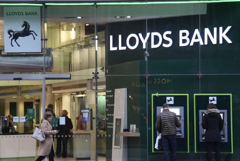Customers use ATMs at a branch of Lloyds Bank in London