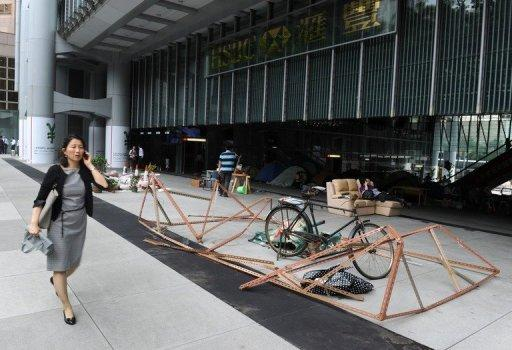 A pedestrian walks past a display by the anti-capitalist Occupy movement in Hong Kong, outside the HSBC building in Hong Kong in June 2012. The camp sprouted at the landmark HSBC tower in central Hong Kong 10 months ago, weeks after thousands of people pitched tents in New York's Zuccotti Park demanding an overhaul of the rules of global capitalism