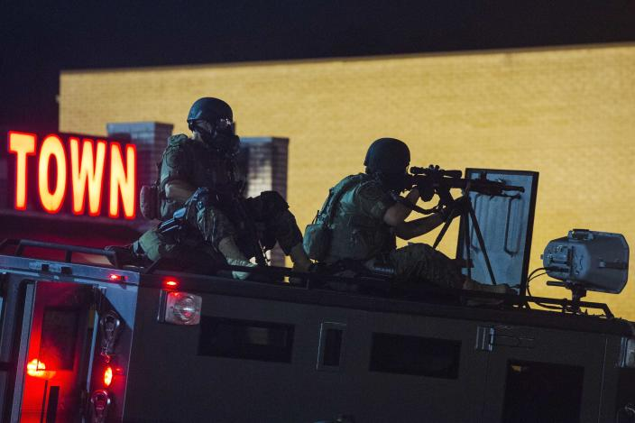 A police sharpshooter looks through his rifle as police monitor a group of rowdy demonstrators during further protests in reaction to the shooting of Michael Brown near Ferguson, Missouri August 18, 2014. Police fired tear gas and stun grenades at protesters in Ferguson, Missouri on Monday, after days of unrest sparked by the fatal shooting of an unarmed black teenager by a white policeman. REUTERS/Lucas Jackson (UNITED STATES - Tags: CIVIL UNREST CRIME LAW SOCIETY)