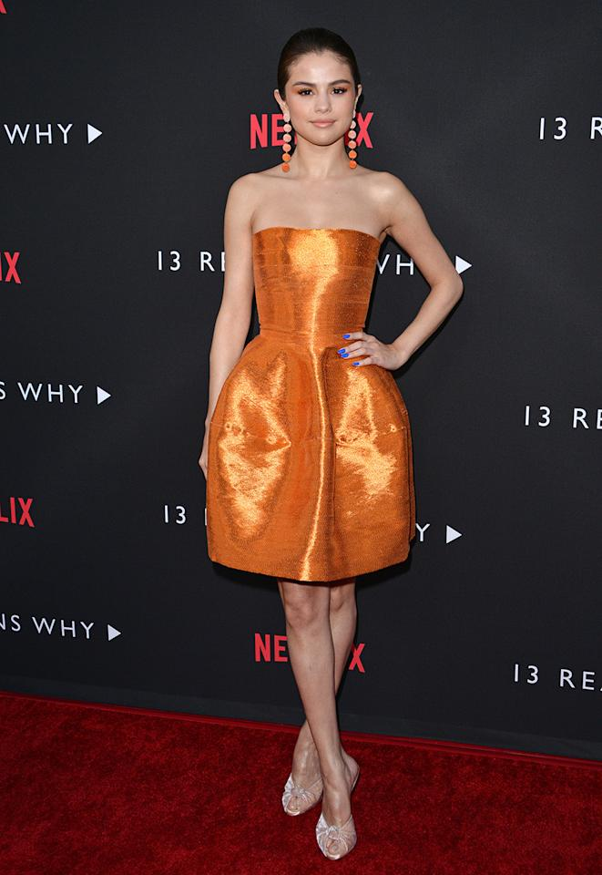 <p>Selena Gomez wore a sophisticated strapless orange minidress from Oscar de la Renta's fall 2017 ready-to-wear collection to the <em>13 Reasons Why</em> premiere in Los Angeles, March 2017. (Photo: Getty Images) </p>
