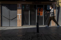A woman wearing a face mask to prevent the spread of coronavirus walks in front of a restaurant displaying a banner To Rent, in downtown Madrid, Spain, Friday, Oct. 9, 2020. Spanish Prime Minister Pedro Sanchez is holding a Cabinet meeting to consider declaring a state of emergency for Madrid in order to impose stronger anti-virus restrictions on reluctant regional authorities. (AP Photo/Manu Fernandez)