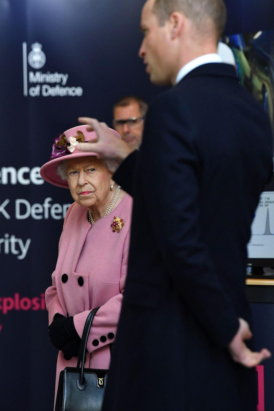 Britain's Queen Elizabeth II (L) looks on as Britain's Prince William, Duke of Cambridge (R) asks a question about forensics work