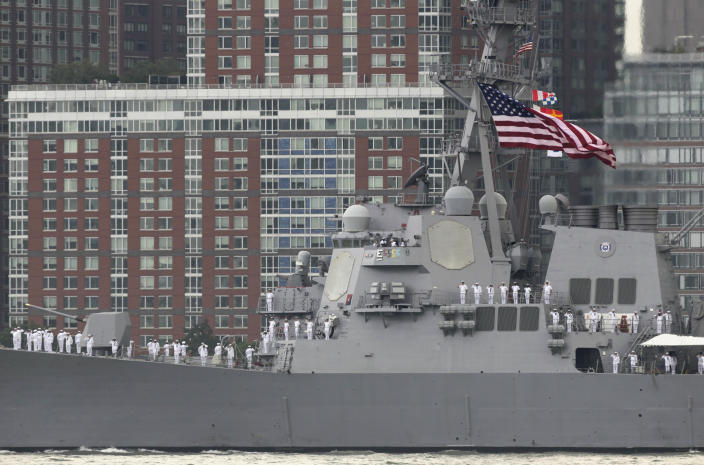 Sailors on the USS Roosevelt stand at attention as they pass the World Trade Center site as seen from Jersey City, N.J., Wednesday, May 23, 2012. Naval vessels ranging from a U.S. amphibious assault ship to a Finnish minelayer are participating in New York City's Fleet Week. (AP Photo/Seth Wenig)