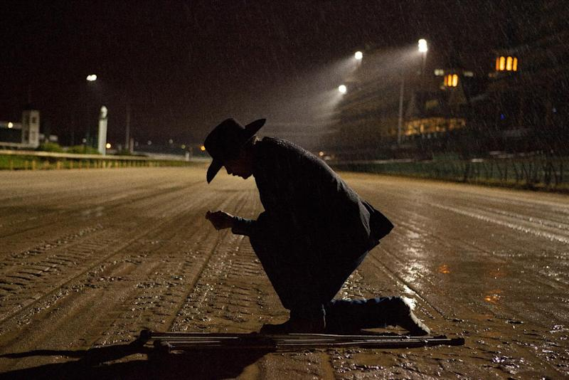 "In this Oct. 14, 2012 image provided by Allied-THA, Chip Woolley, played by actor Skeet Ulrich, kneels on the muddy racetrack in a scene from the movie ""50-1."" (AP Photo/Courtesy of Allied-THA."
