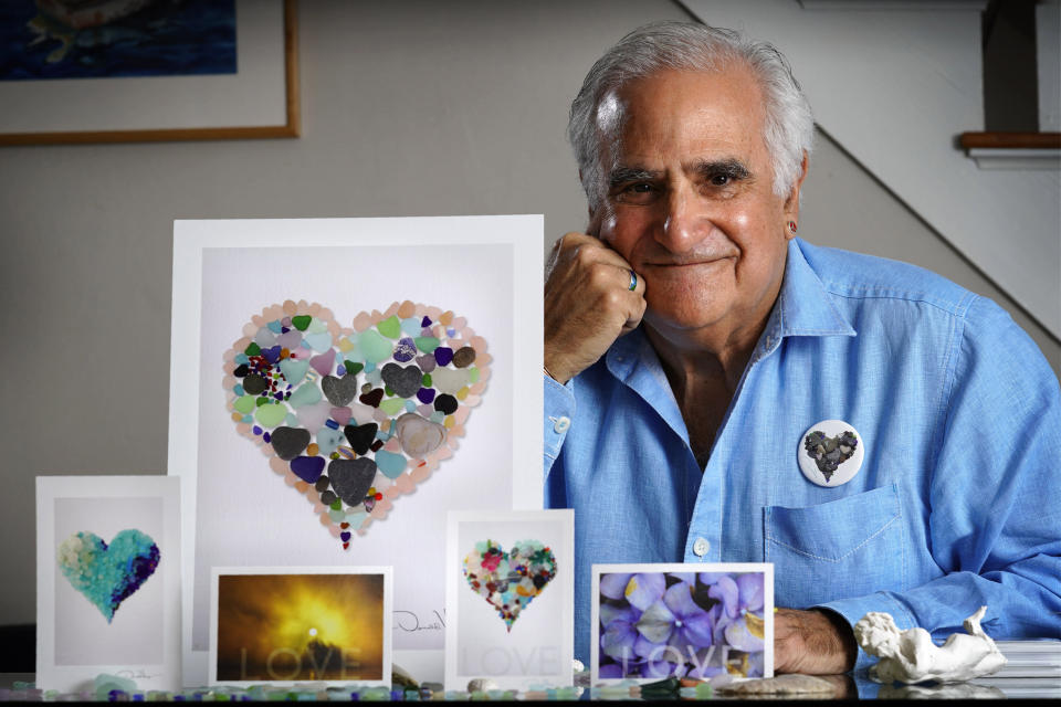 Artist Donald Verger poses with his images of sea glass, landscapes and flowers, Thursday, Feb. 11, 2021, in Falmouth, Maine. Verger, who has donated his photography to schools and hospitals, said he considers his small but colorful contribution a way of bringing a smile to people's faces during the ongoing pandemic. (AP Photo/Robert F. Bukaty)