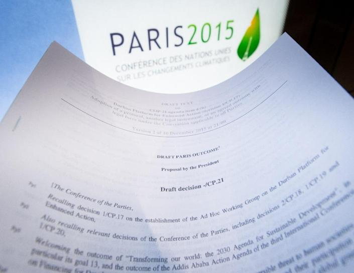 An illustration picture taken on December 10, 2015 in Paris shows a draft for the outcome of the COP21 United Nations conference on climate change next to the logo of the summit (AFP Photo/Benoit Doppagne)